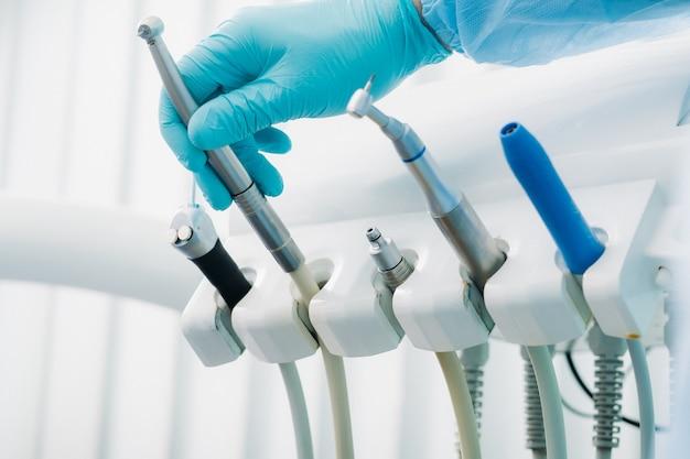 Стоматолог в перчатках в стоматологическом кабинете держит инструмент перед работой.