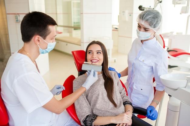 Стоматолог с ассистентом подберут цвет зубов красивой девушке