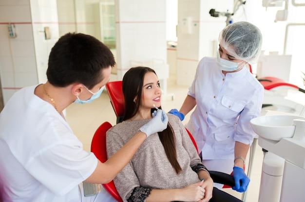 Стоматолог с ассистентом подберут цвет зубов красивой девушке.