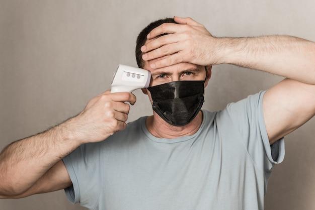 Депрессивный мужчина в защитной маске готов использовать инфракрасный термометр на лбу для проверки температуры тела на наличие вирусных симптомов - концепция вспышки эпидемического вируса. коронавирус. термометр пистолет
