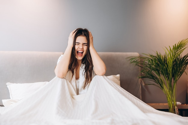 우울한 여성이 침대에 앉아 손으로 귀를 막습니다. 흰 잠옷을 입은 젊은 여성이 침대에 앉아서 비명을 지르고 있습니다.