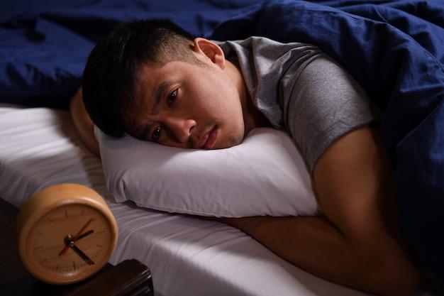 Молодой человек в депрессии, страдающий бессонницей, лежит в постели
