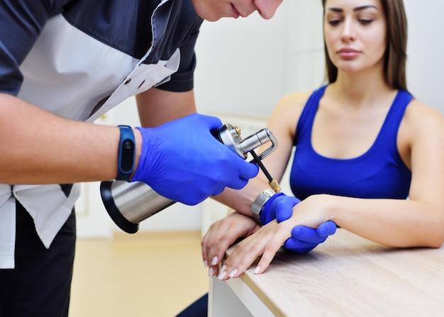 皮膚科医が女性を診察し、特別な器具である低温破壊器を持っています。