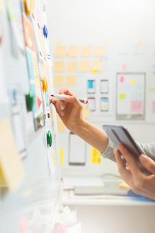 デザイナーがウェブサイトプロジェクトのスケッチを描きます。モバイルアプリケーションインターフェイス開発者。