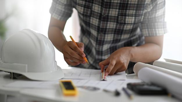 デザイナーが事務用品を置いた机の上の家のインテリアを描いています。