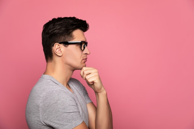 디자이너. 회색 티셔츠와 안경을 쓴 똑똑한 남자는 왼손으로 턱을 만지고 프로필에 서서 무언가를 생각하고 있습니다.
