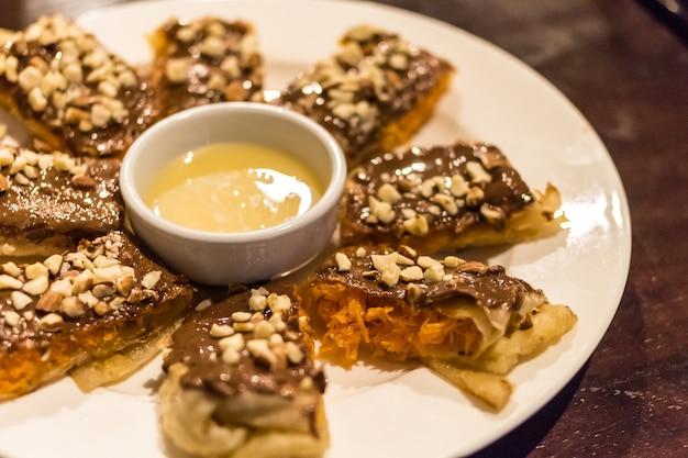 Десерт тайский шоколад roti с арахисом и сливочным молочным соусом на белом блюде из дерева
