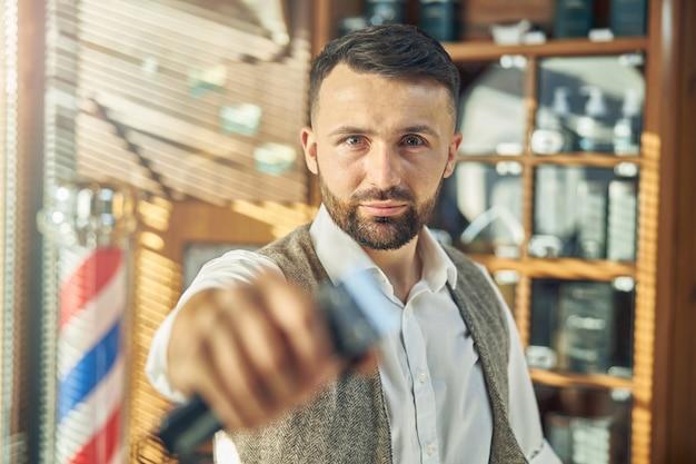 バリカンを持ってカメラを見ている理髪店で働く決意の若い男