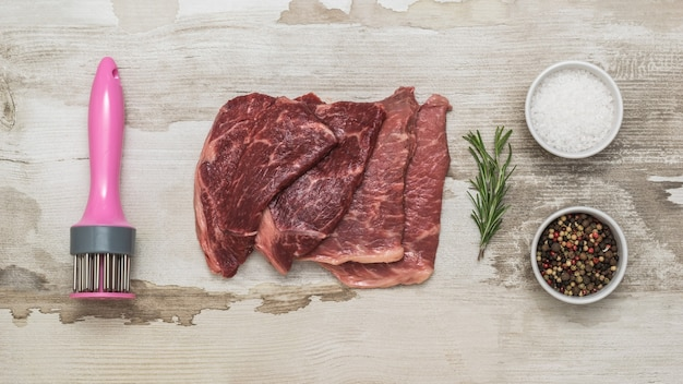 Устройство для приготовления отбивных и стейков из говядины на деревянном столе. мясное блюдо.