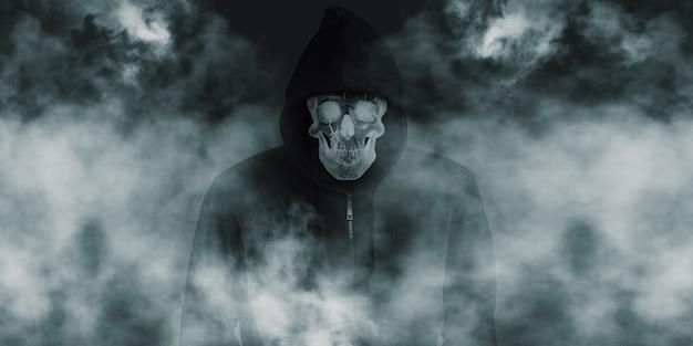 후드와 검은 셔츠 아래 웃는 연기 두개골과 검은 가운에 악마 두개골