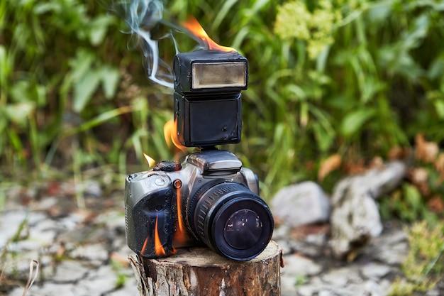 Цифровой фотоаппарат охвачен пламенем в туристическом лагере во время лесного пожара.
