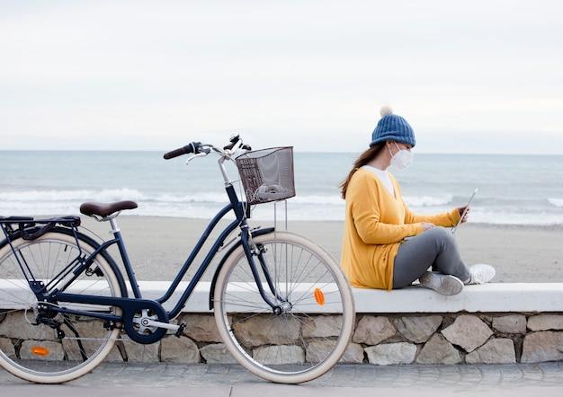 Специалист по цифровому маркетингу работает над новым проектом по продвижению ноутбука, сидя на велосипеде на набережной. независимая женщина общается с клиентами.