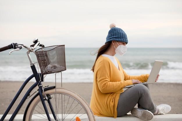Цифровой маркетолог в маске работает над новым проектом по продвижению ноутбука, сидя на променаде с велосипедом. независимая женщина общается с клиентами.
