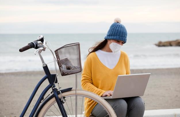 フェイスマスクを着用したデジタルマーケティング担当者が、自転車で遊歩道に座って、新しいノートパソコンのプロモーションプロジェクトに取り組んでいます。独立した女性はクライアントと通信します。
