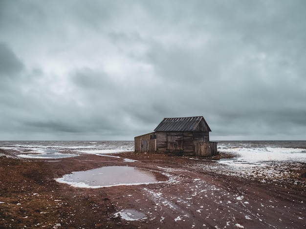 백해 연안의 정통 마을에있는 낡은 늙은 어부의 오두막. 콜라 반도의 움바 마을. 러시아.