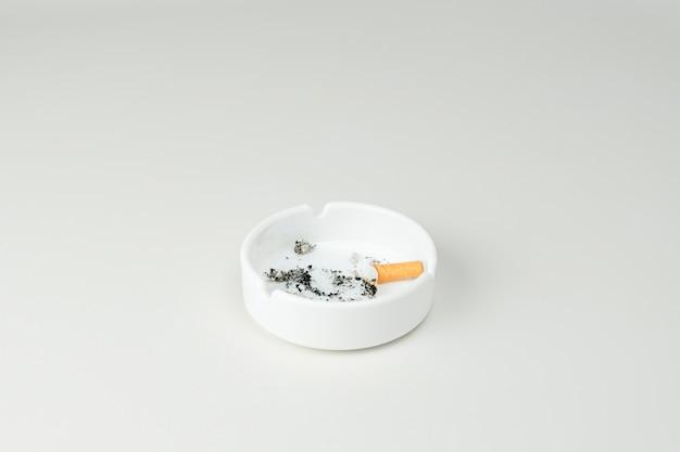 Грязная пепельница с пеплом от сигарет и окурком