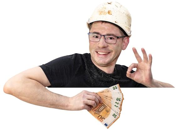 건설용 헬멧을 쓴 더러운 남자가 손에 유로 지폐를 들고 있습니다. 손으로 확인 표시를 보여줍니다. 격리 된 흰색 배경입니다. 텍스트를 위한 여유 공간입니다. 복사 공간입니다.