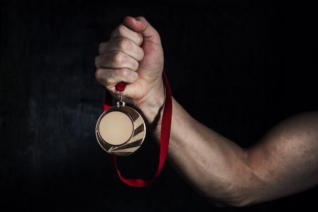 Рука грязного человека держит золотую медаль на темном фоне. концепция успеха