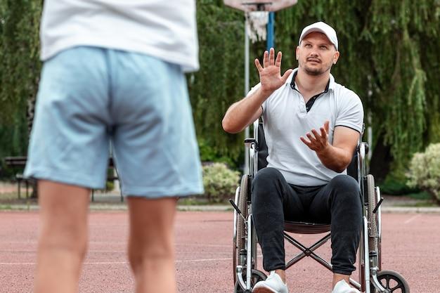障害のあるお父さんは路上で息子と遊んでいます。車いすのコンセプト、身障者、充実した生活、父と息子、活動、陽気。