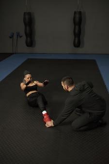 身体の不自由な女の子がジムに従事片足の女性がトレーナーと一緒にトレーニングし、一生懸命働き、トラブルの前で諦めない