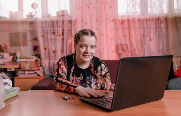 斜めの目を持つ障害のある女の子が机に座ってラップトップで作業しています。障害者のためのトレーニング