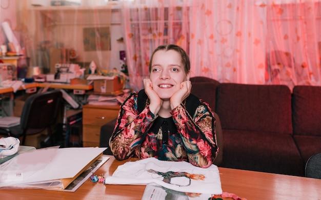 目が傾いた障害のある少女がテーブルに座って微笑む。障害を持つ人々。