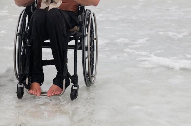 冬に車椅子の障害者が氷の中の冷たい水で泳ぐつもりです
