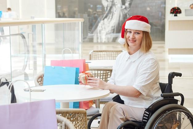 ショッピングバッグとサンタの帽子をかぶっている障害のある女性