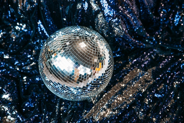 디스코 미러 볼은 반짝임이있는 파란색 섬유에 놓여 있습니다.