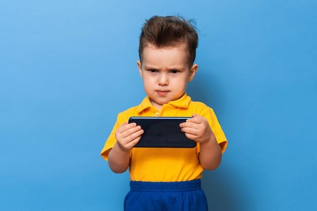 Недовольный мальчик держит в руках мобильный телефон. фото на синей стене.