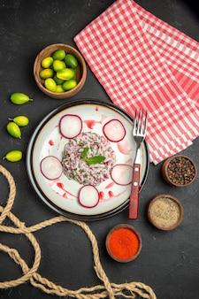 赤みがかったフォークの柑橘系の果物のスパイスと市松模様のテーブルクロスの料理