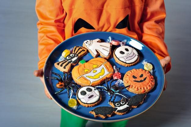 ハロウィーンのためのオリジナルの装飾されたジンジャーブレッドクッキーと子供の手にある料理