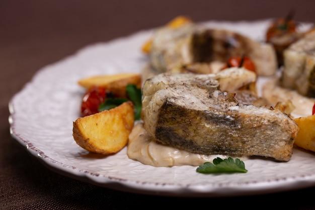 Блюдо из кусочков рыбы на белом в ресторане.