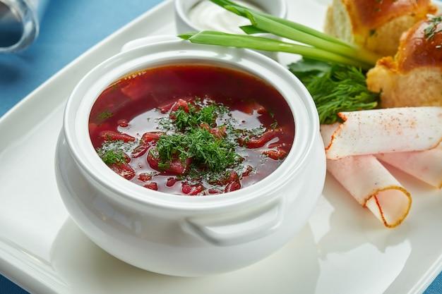 Блюдо украинской кухни - наваристый борщ из свинины с пампушкой, зеленым луком и салом в белой тарелке на синей скатерти.