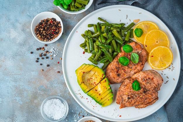 灰色のコンクリートの背景に鶏肉と野菜、レモンとアボカドを添えた料理。