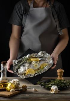 Блюдо из рыбы дорадо, запеченное в фольге в руках шеф-повара.