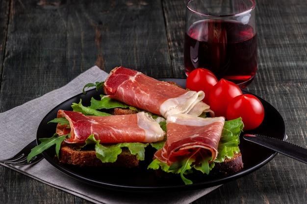 잼, 허브, 토마토 및 와인 한 잔이 들어간 샌드위치가 나무 테이블에 서있는 접시