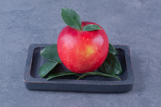 Яблоко на деревянной тарелке на мраморном столе.