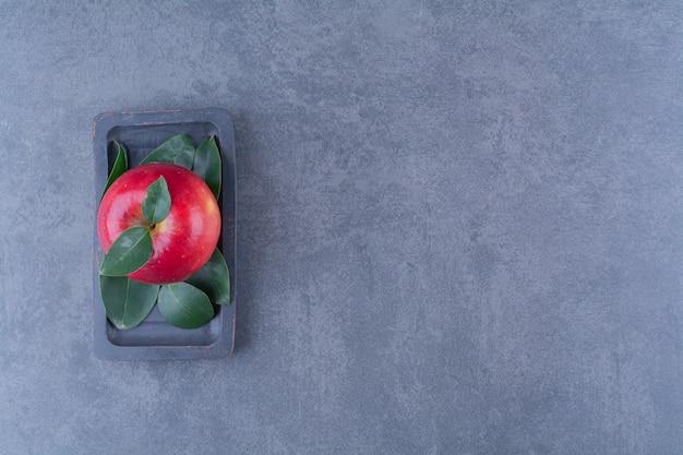 Яблоко на деревянной тарелке на темной поверхности