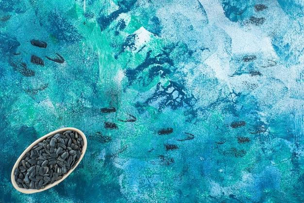 Выставка неочищенных семечек на миске на мраморном столе.