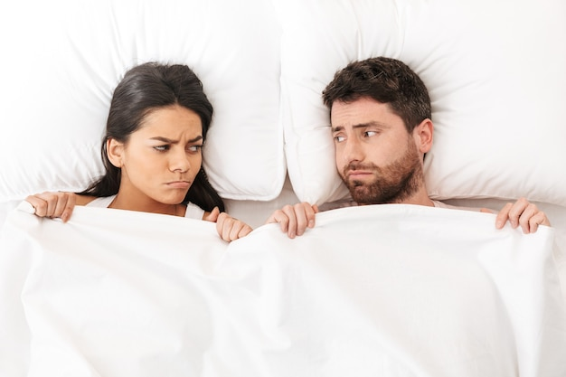 不機嫌な喧嘩若い愛情のあるカップルは毛布の下のベッドに横たわっています