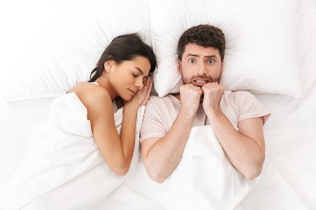 Недовольный шокированный испуганный растерянный молодой человек лежит в постели под одеялом рядом со спящей женщиной