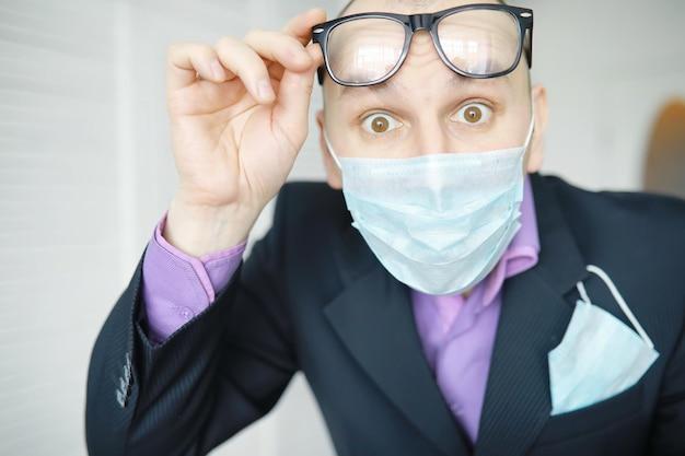 ナプキンの代わりに使い捨ての医療用マスクがポケットから突き出ています。スーツとジーンズに使い捨てマスクを持った男。個々の呼吸保護。