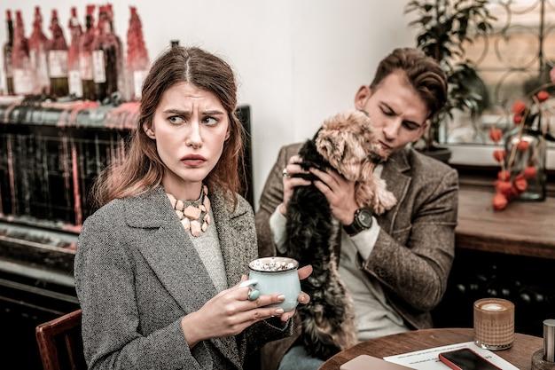 Распределение внимания. женщина расстроена из-за того, что ее партнер уделяет внимание только своей собаке.