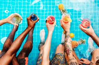 A diverse group of friends enjoying summer time with beverages in hands
