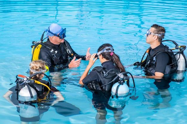 다이빙 강사가 그룹의 사람들에게 다이빙을 가르칩니다.