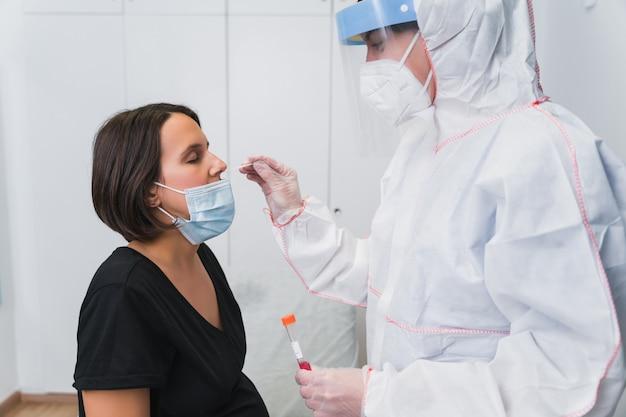 Врач проводит пцр для обнаружения covid 19 у беременной женщины в кабинете врача