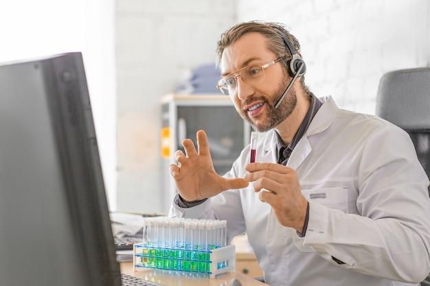 患者とのオンライン相談中に医師が血液サンプルの入った試験管を見せます。医療と医学における現代技術の概念。
