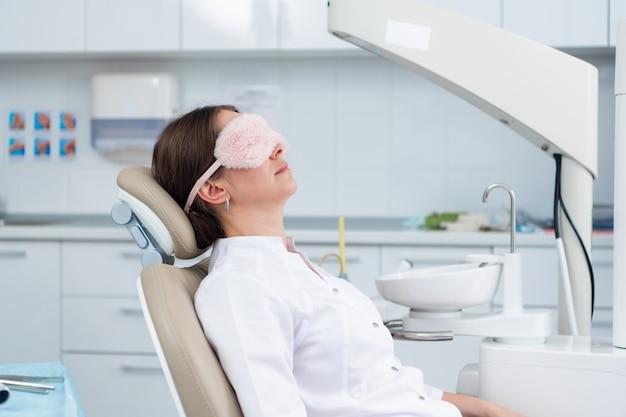 Врач дремлет в стоматологическом кресле с помощью маски для сна