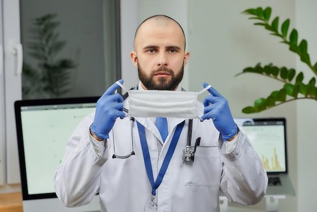 コロナウイルス(covid-19)の拡散を防ぐために、保護マスクを手に持った医師。
